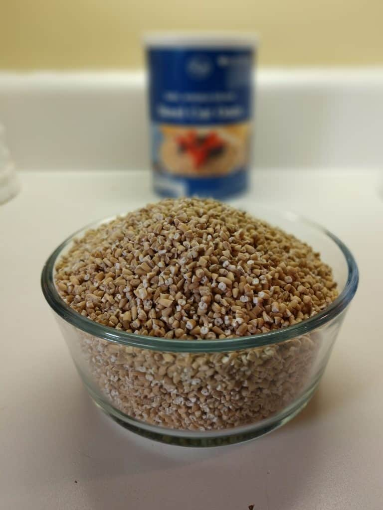 bowl of precooked steel cut oats with steel cut oats container in the background