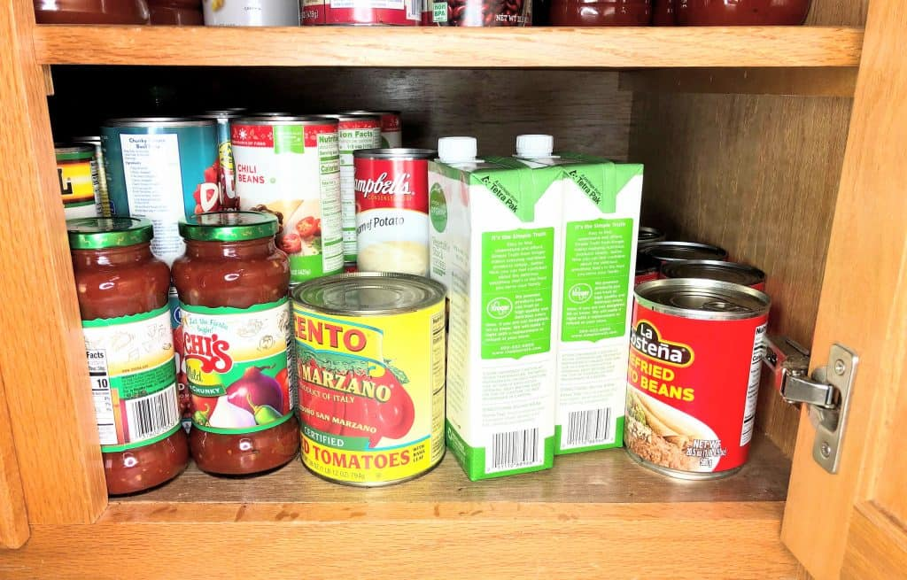 cabinet with rows of vegetable stock, refried beans, salsa, tomatoes, and soup