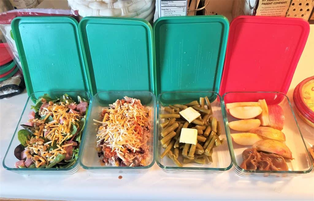 pyrex dishes with salad, burrito bowl, green beans, and apple slices with peanut butter
