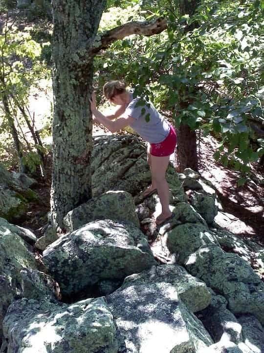 woman walking on rocks along hiking trail
