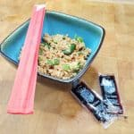 bowl of vegetable fried rice with chopsticks and soy sauce packets