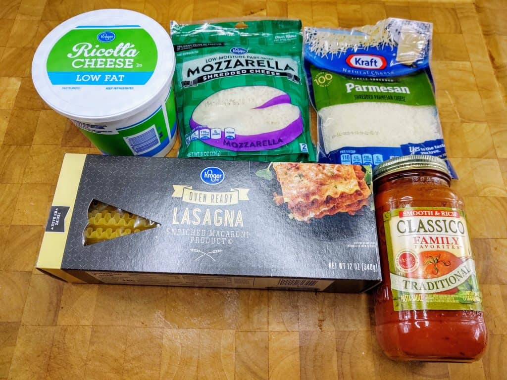 ingredients grouped together. top from left: Ricotta cheese, mozzarella cheese, Parmesan cheese, lasagna noodles, jar of pasta sauce.
