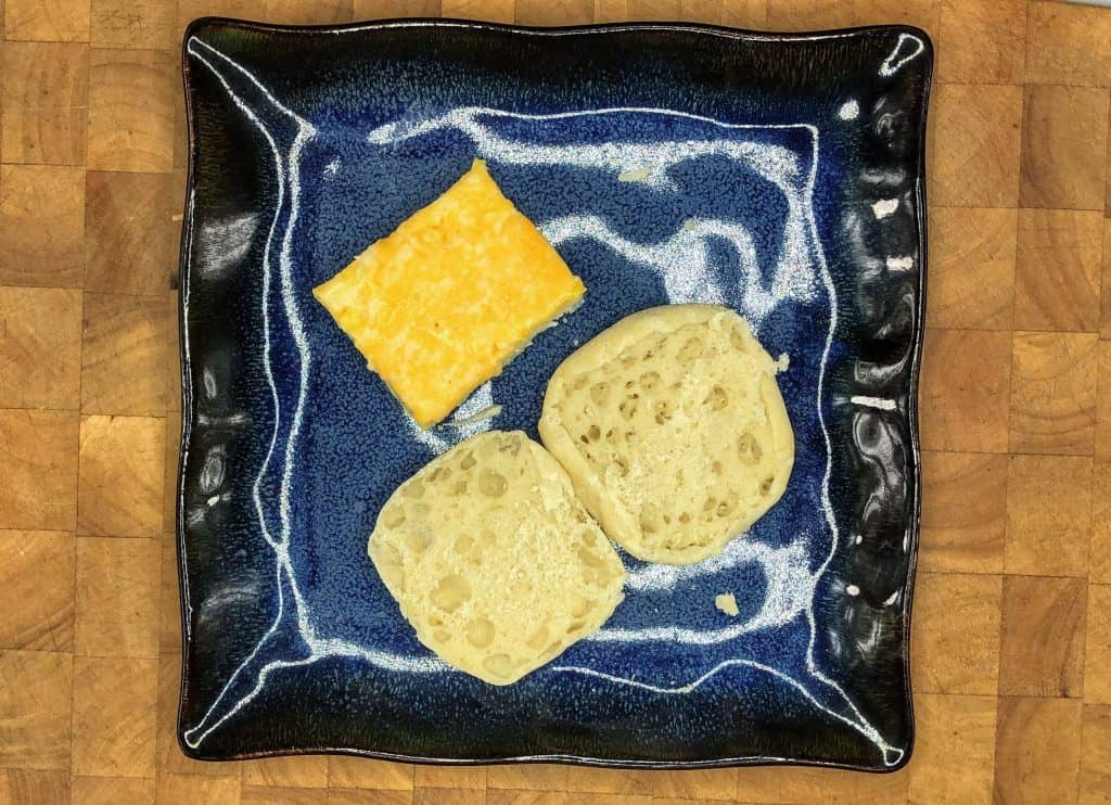 english muffin open on plate next to egg square with cheese