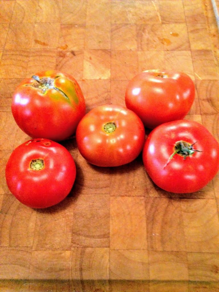 featured image for how to grow tomatoes. 5 garden fresh tomatoes on counter top