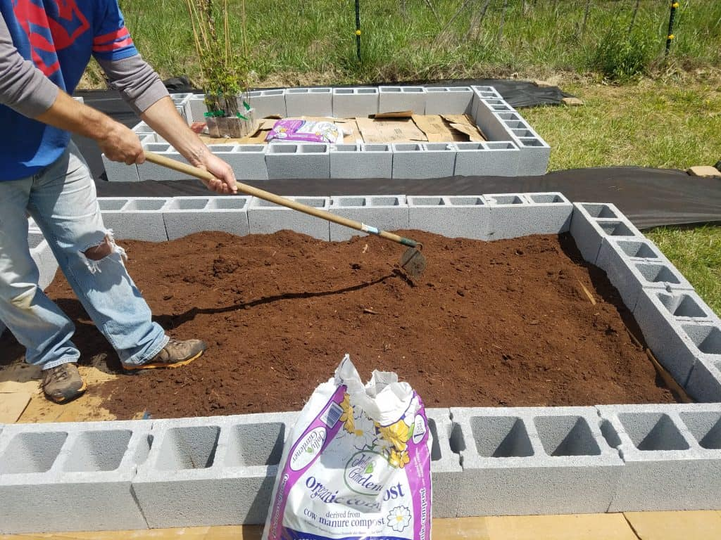 adding and working soil in raised bed