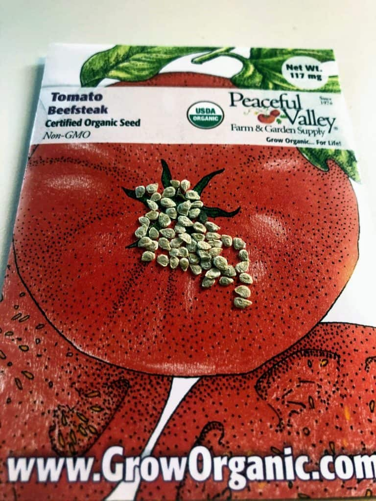 beefsteak tomato seed packet with seeds on top