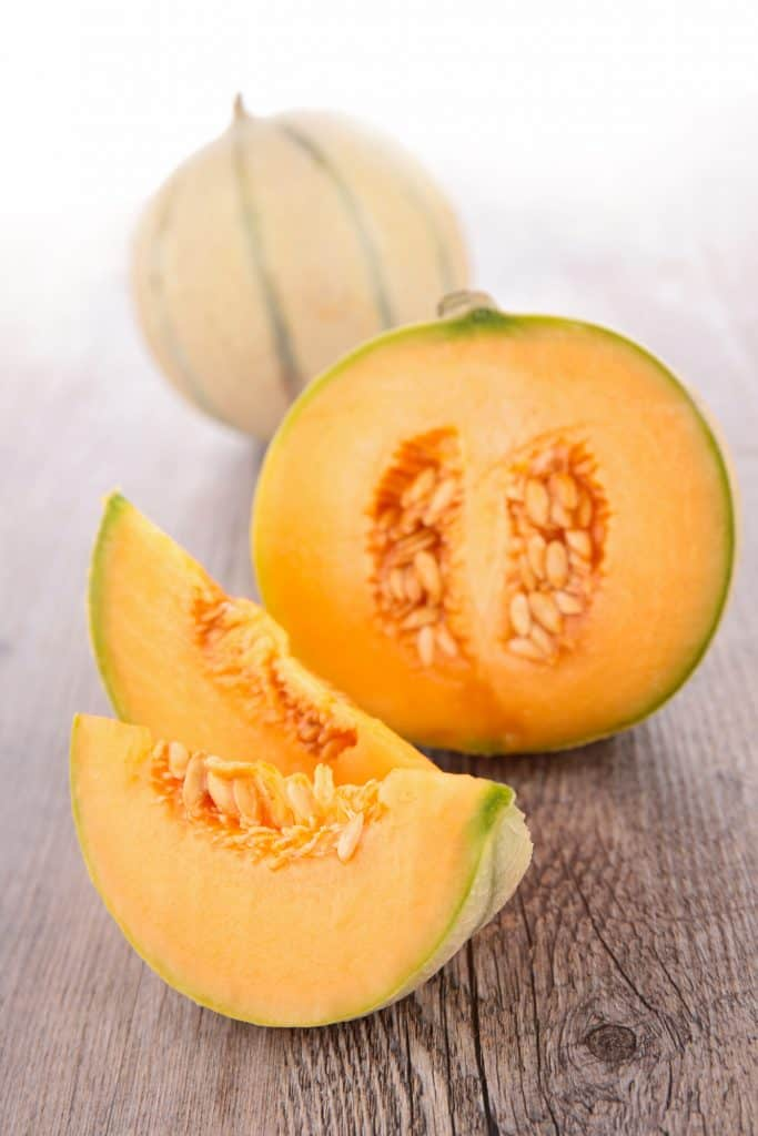 cantaloupe cut into wedges on wood counter